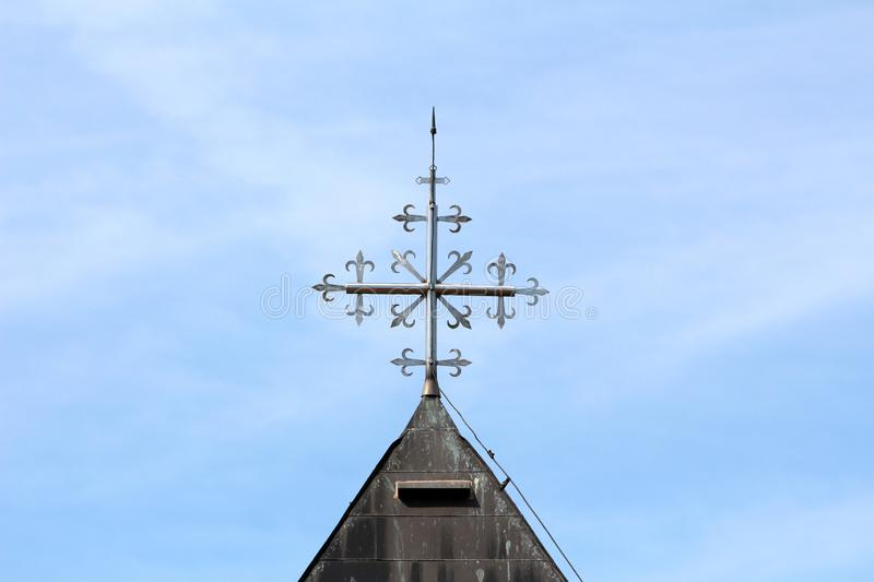 Unusual shiny metal cross on top of old local church roof surrounded with lightning rod and dilapidated metal roof tiles stock photography