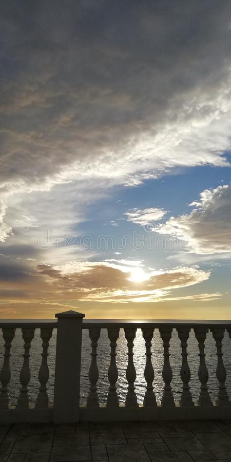 Unusual spiral clouds against the backdrop of the sea sunset and the classic balustrade. Beautiful alarming admiring natural. Unusual sea sunset on the stock images