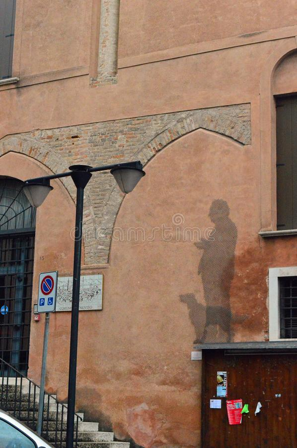 Terracotta coloured plasters building with `mural` of man walking dog made out of wire mesh. Unusual Street art - Terracotta coloured plastered building with ` royalty free stock photo
