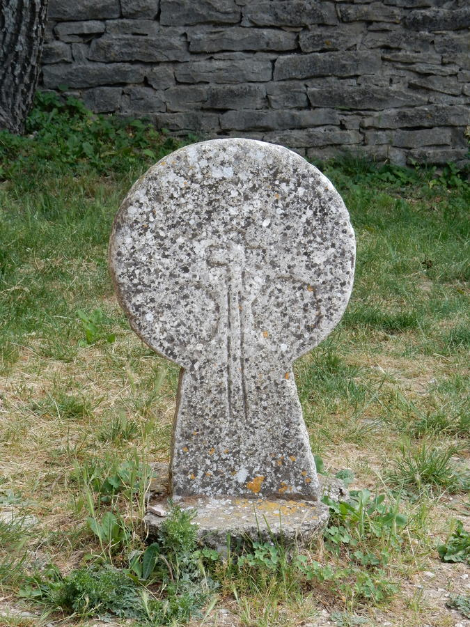Unusual Templar head stone. Granite with some engraving visible dry stone wall and grass in background stock photos