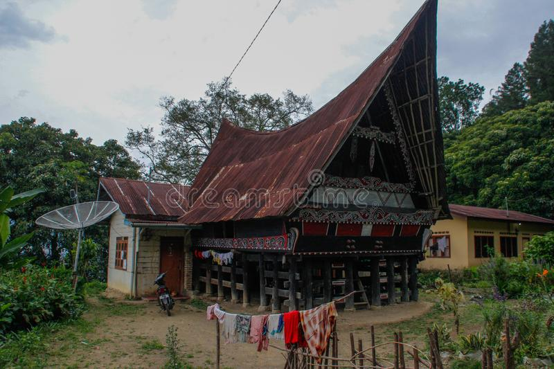Unusual traditional houses with boat roofs of the Batak people on the island of Sumatra, Indonesia. The traditional architecture o. Parapat, Sumatra - January 30 stock photography