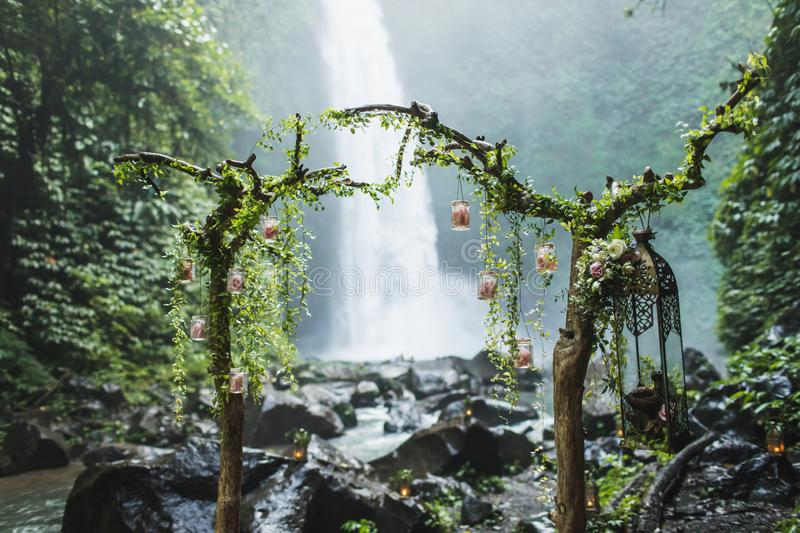 Unusual wedding ceremony arch with waterfall view in jungle rainforest. Dream Wedding ceremony in Bali stock photo