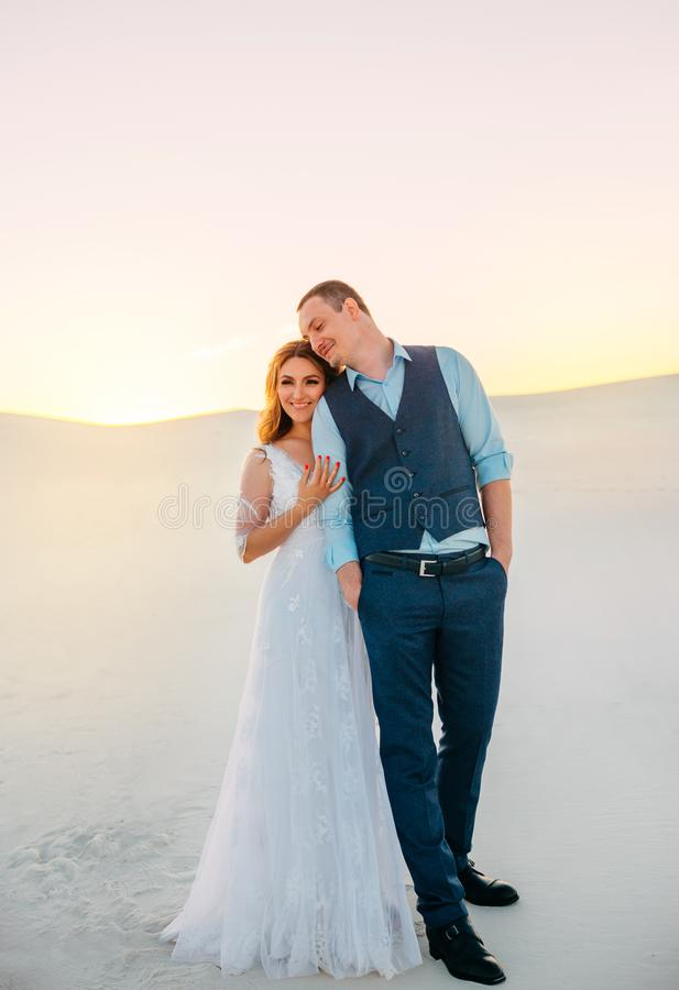 Unusual wedding photo shoot in the desert. Background white sands at sunset. Happy brunette girl with long hair hugging stock photos
