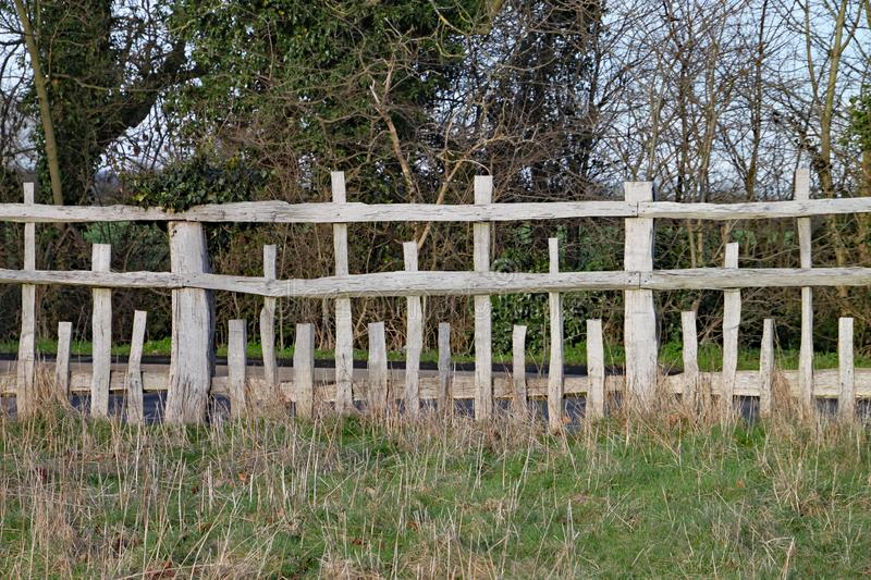 Unusual wooden fence with parallel horizontal rails and vertical posts of different lengths in a pattern stock photo