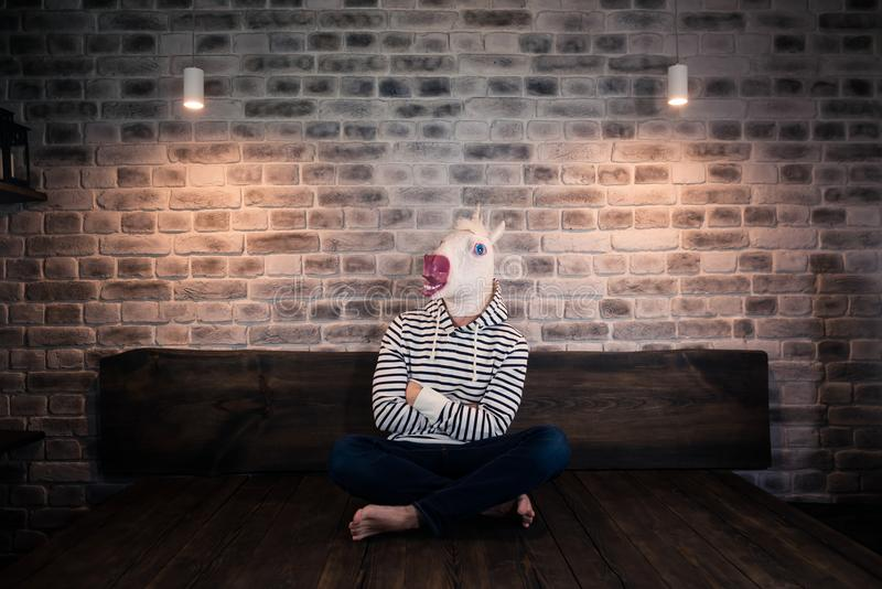 Unusual young man in comical mask sits alone on the bed stock image