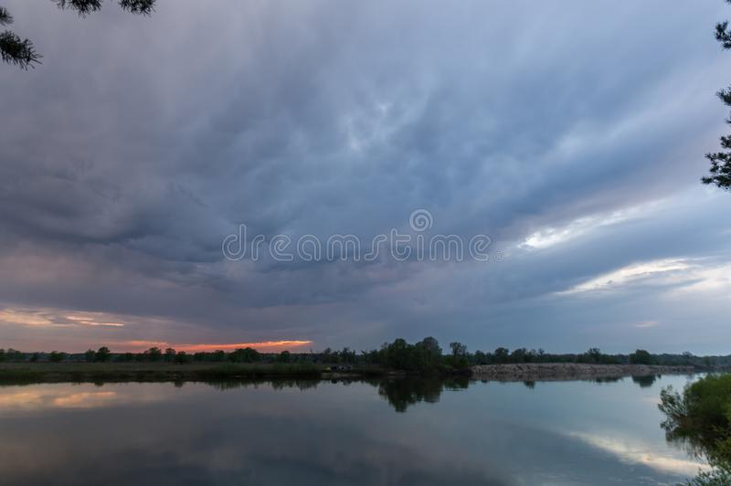 Unusually beautiful sky over the river. Unusual landscape in cloudy weather. Dark overcast sky royalty free stock photos