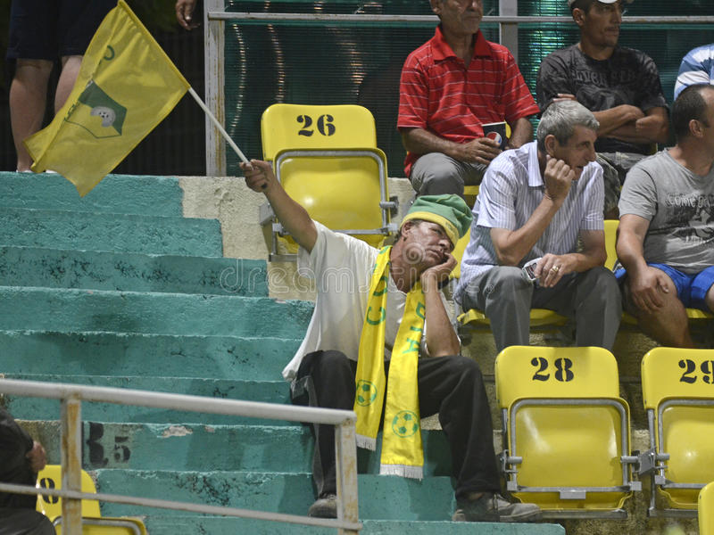 Unusually bored football fan. Old man football fan cheering bored for his team during the Romanian League game between Concordia Chiajna and CFR Cluj on August