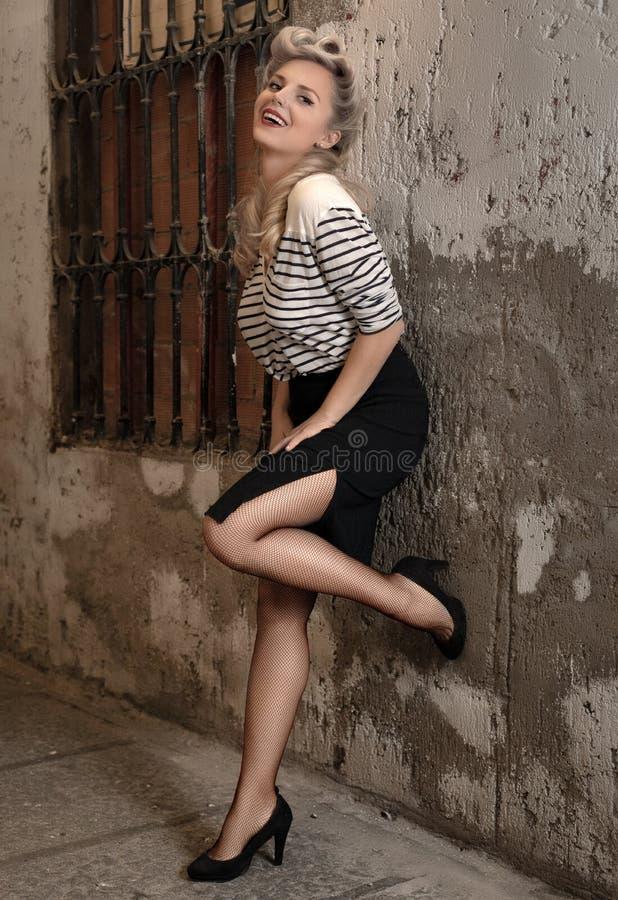 Unverschämte Blondine mit einer Retro- Frisur lächelt an der Kamera lizenzfreie stockfotografie