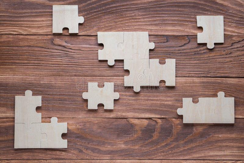 Unvollst?ndige h?lzerne Puzzlespiele auf braunem h?lzernem Schreibtisch, Draufsicht, flache Lage stockfoto
