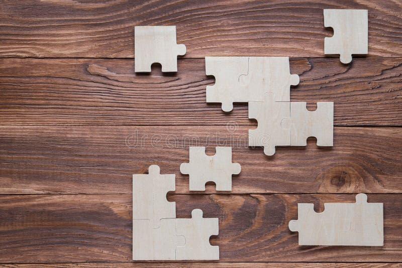 Unvollst?ndige h?lzerne Puzzlespiele auf braunem h?lzernem Schreibtisch, Draufsicht, flache Lage lizenzfreies stockbild
