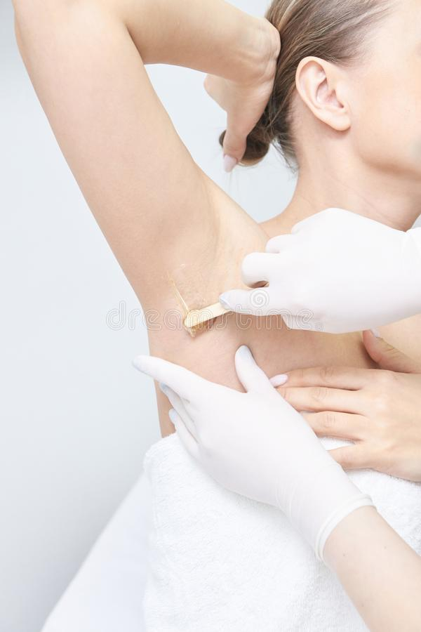 Unwanted hair wax epilation. Young Woman. cosmetology salon treatment procedure. Home waxing.  stock photography