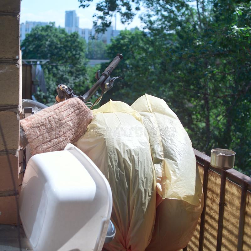 Unwanted stuff on a messy balcony. A cityscape in the blurred background royalty free stock photos