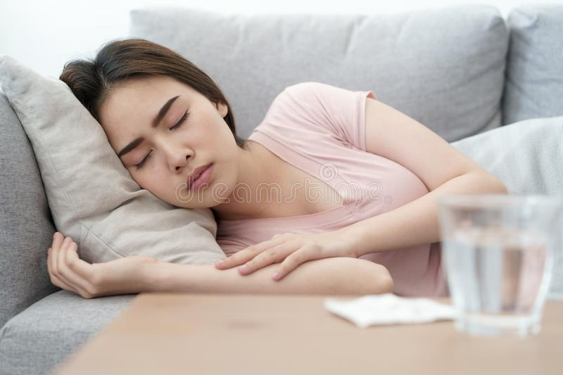 Unwell condition young Asian girl sleeping on sofa after checking temperature and taking medicines and water, Health and illness. Concepts royalty free stock photography