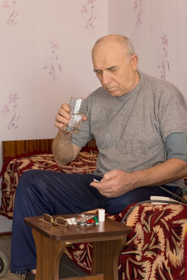 Unwohler älterer Mann, der Medizin nimmt stockbild