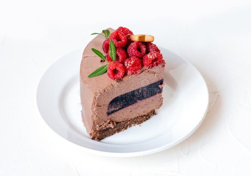 Unzählbare Scheibe der Schokolade des Kuchens auf Platte, mit Himbeeren auf weißem Hintergrund, mit grünen Blättern Klumpen der S lizenzfreie stockfotos