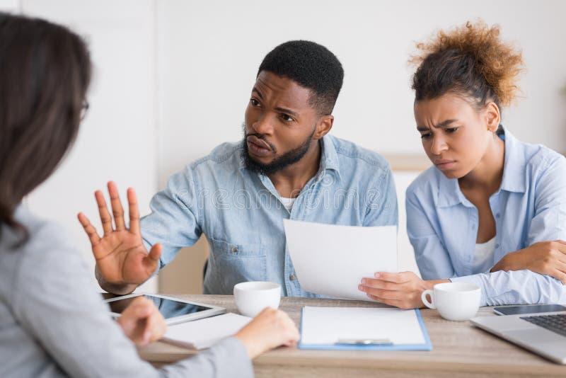 Unzufriedene Afroamerikanerpaare, die den Rat des Versicherungsmaklers kritisieren und zurückweisen stockbild