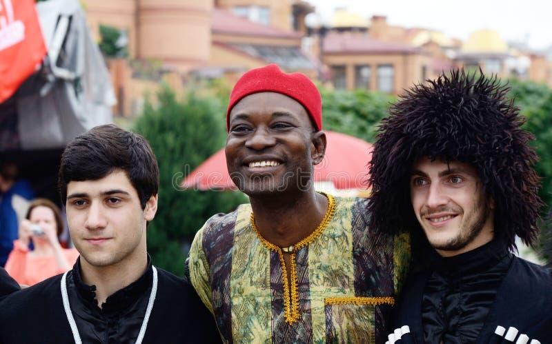 Uomini africani e georgiani in vestiti tradizionali che preparano alla prestazione al giorno della festa di Kiev fotografia stock libera da diritti