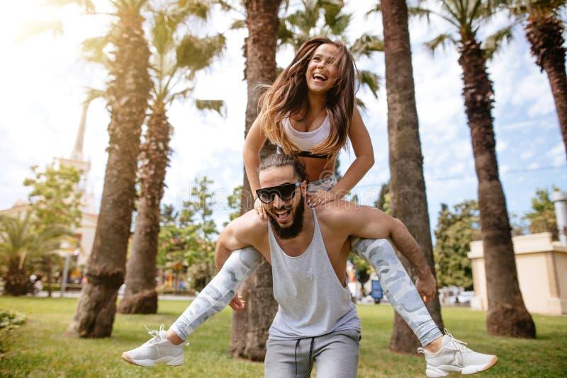 Uomini allegri allegri che danno sulle spalle giro alle donne al parco tropicale immagine stock libera da diritti