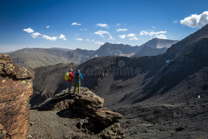 Uomini anonimi che ammirano vista delle montagne fotografie stock