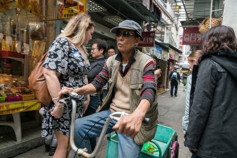 Uomini asiatici che ciclano nel villaggio del Tai O fotografia stock libera da diritti