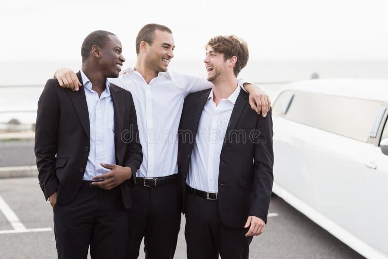 Uomini bei che posano accanto alle limousine fotografie stock libere da diritti