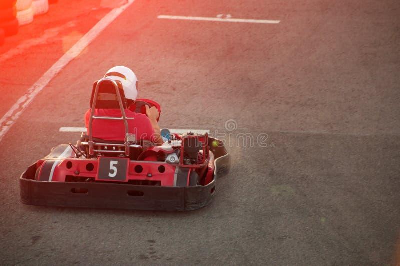 Uomini che conducono automobile da go-kart con velocità in una pista di corsa del campo da giuoco immagini stock libere da diritti