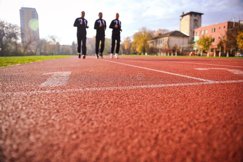 Uomini che corrono sui vicoli della pista di atletica fotografia stock