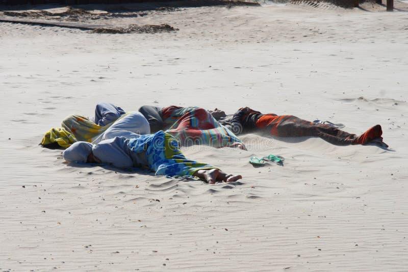 Uomini che dormono sulla spiaggia fotografia stock