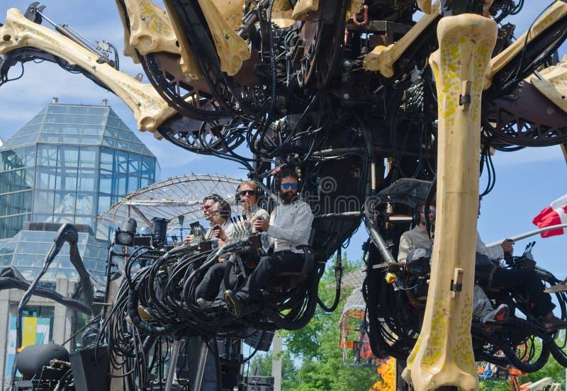 Uomini che fanno funzionare le gambe di Kumo un ragno gigante in Ottawa