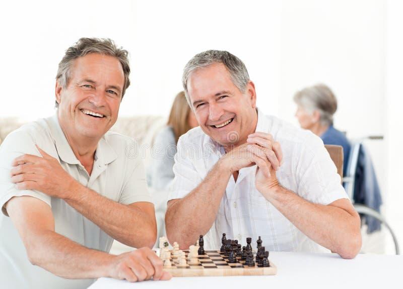 Uomini che giocano scacchi mentre i loro wifes stanno comunicando fotografia stock libera da diritti