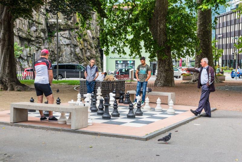 Uomini che giocano scacchi su un insieme gigante fotografia stock