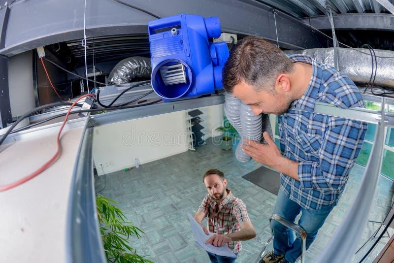 Uomini che inseriscono tubo flessibile nel roofspace immagine stock libera da diritti