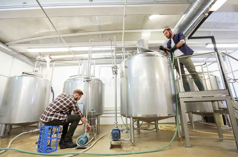 Uomini che lavorano ai bollitori della fabbrica di birra della birra del mestiere fotografia stock