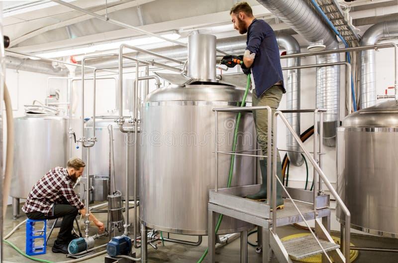 Uomini che lavorano ai bollitori della fabbrica di birra della birra del mestiere fotografia stock libera da diritti