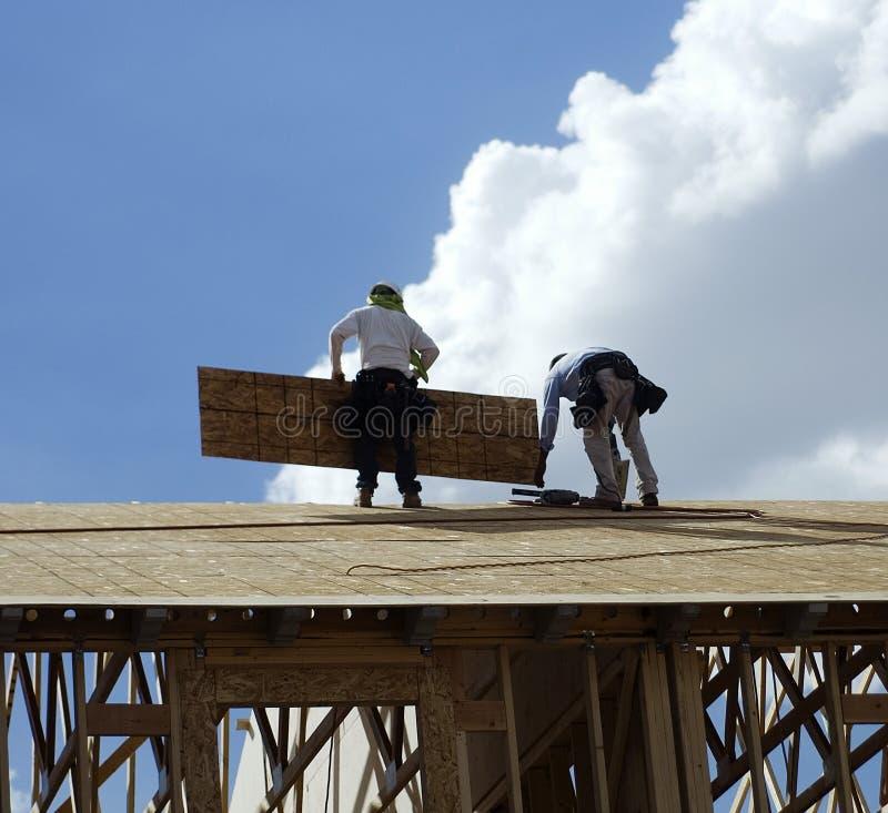 Uomini che lavorano alla parte superiore del tetto immagini stock