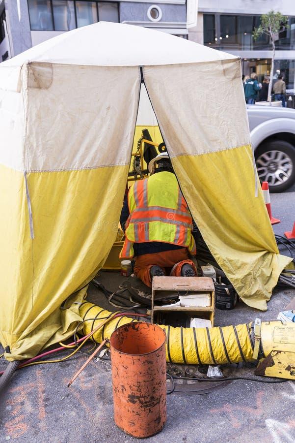 Uomini che lavorano alla tenda della via della città in isolamento immagine stock libera da diritti
