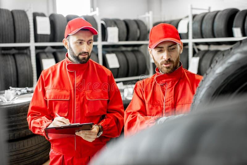 Uomini che lavorano nel magazzino con le gomme fotografia stock libera da diritti
