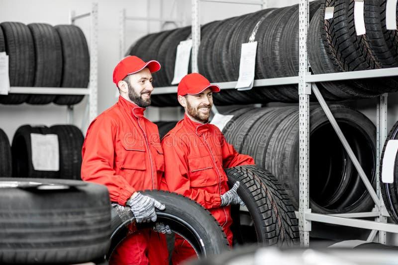 Uomini che lavorano nel magazzino con le gomme immagine stock