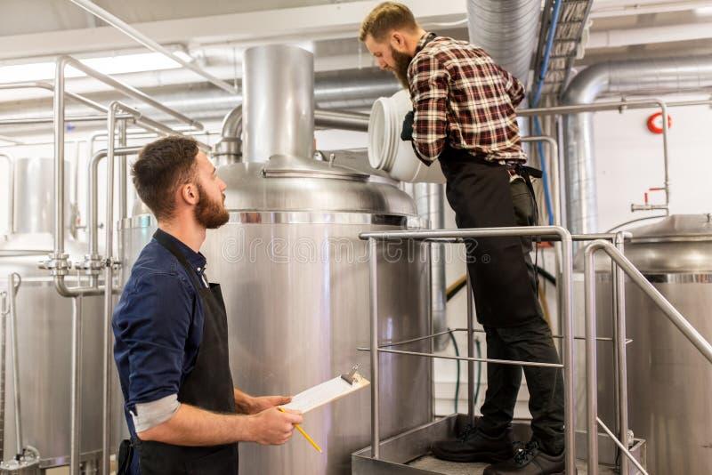 Uomini che lavorano nella fabbrica di birra del mestiere o nella pianta della birra fotografie stock libere da diritti