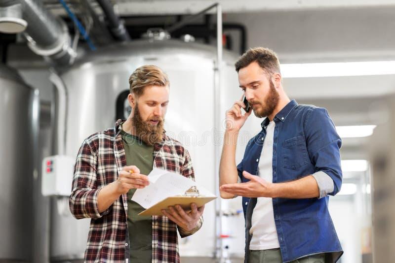 Uomini che lavorano nella fabbrica di birra del mestiere o nella pianta della birra fotografie stock