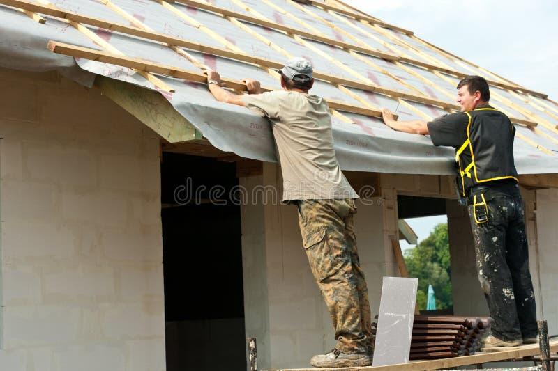 Uomini che mettono tetto su una casa   fotografia stock libera da diritti