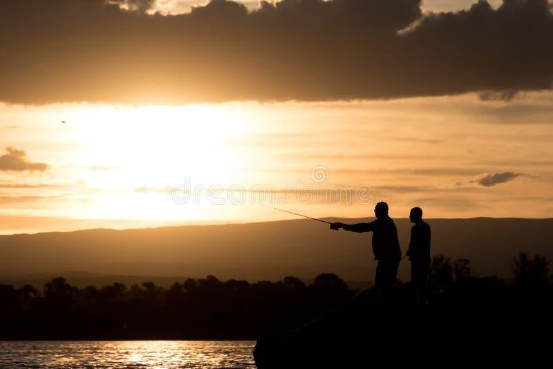 Uomini che pescano nel lago al tramonto fotografia stock