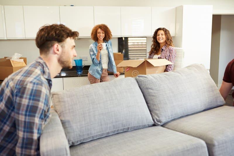 Uomini che portano la nuova casa di Sofa Helping With Move Into immagine stock