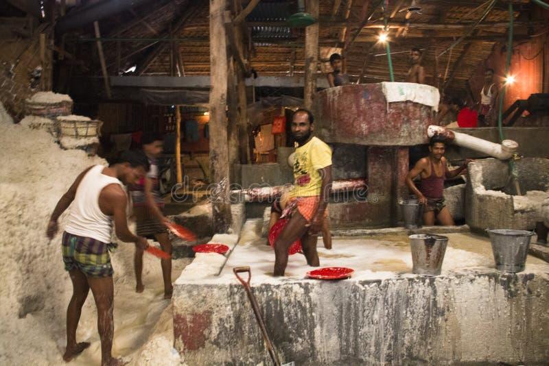 Uomini che puliscono sale in una fabbrica a Chittagong, Bangladesh immagini stock