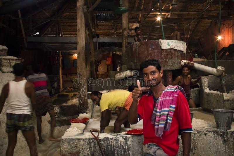 Uomini che puliscono sale in una fabbrica a Chittagong, Bangladesh fotografie stock libere da diritti