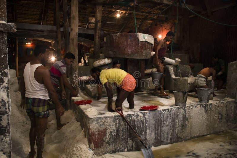 Uomini che puliscono sale in una fabbrica a Chittagong, Bangladesh fotografia stock libera da diritti