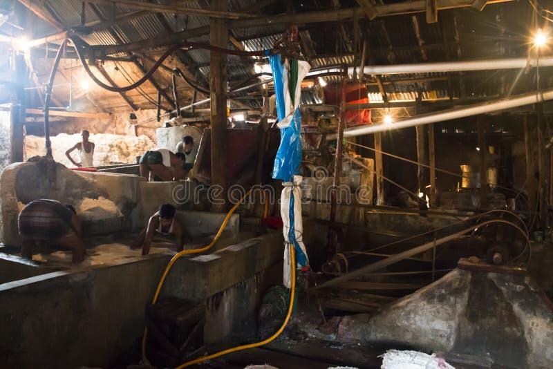 Uomini che puliscono sale in una fabbrica a Chittagong, Bangladesh immagine stock