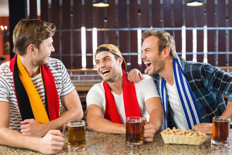Uomini che ridono con le birre in mani fotografie stock libere da diritti