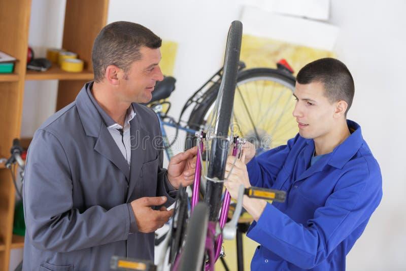 Uomini che riparano pushbike in officina immagini stock