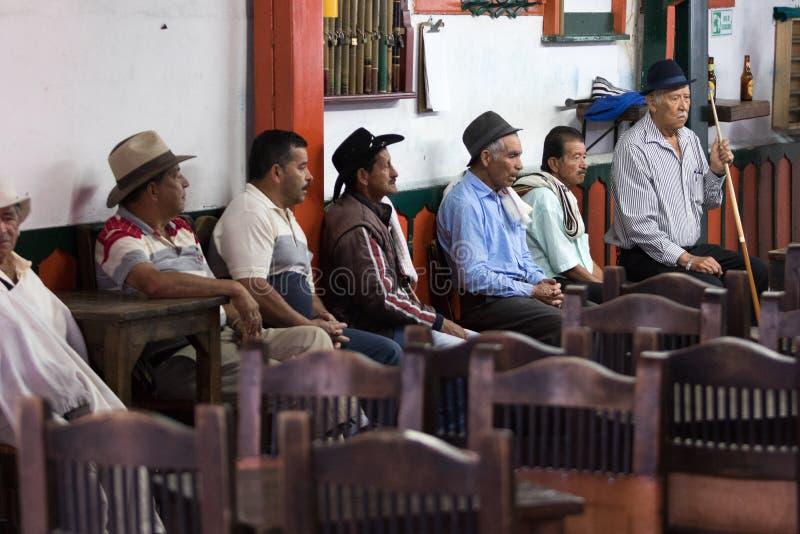Uomini che si siedono dentro una barra in Salento Colombia fotografia stock